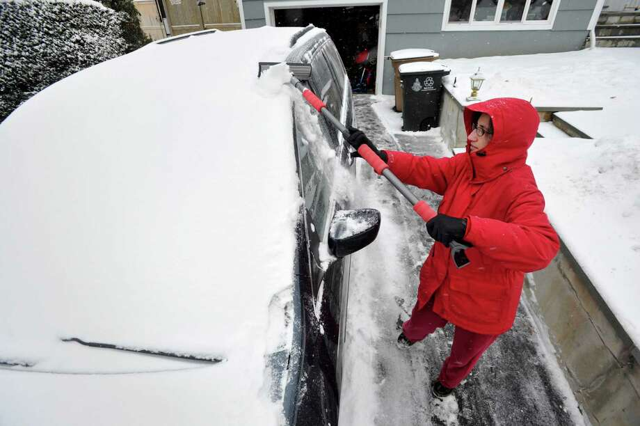 Amy Notter clears snow off her car after the mild snow storm in Stamford, Conn., on Tuesday, Dec. 17, 2013. Photo: Jason Rearick / Stamford Advocate