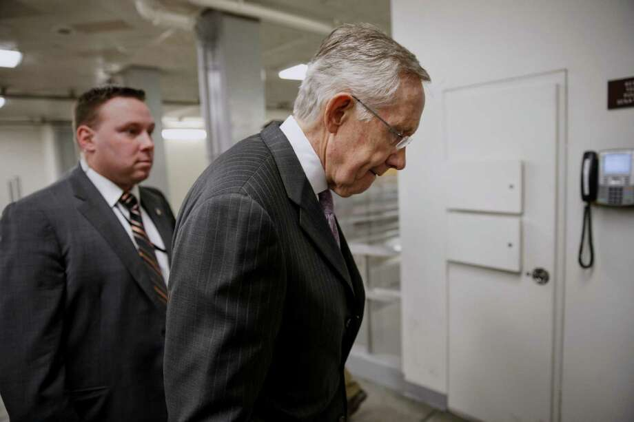 Senate Majority Leader Harry Reid of Nev. walks on Capitol Hill in Washington, Tuesday, Dec. 17, 2013, as he takes a break from the floor after a bipartisan budget compromise cleared a procedural hurdle, advancing past a filibuster threshold on a 67-33 vote that ensures the measure will pass the Democratic-led chamber no later than Wednesday and head to the White House to be signed into law. When enacted, the measure would ease for two years some of the harshest cuts to agency budgets required under automatic spending curbs commonly known as sequestration. (AP Photo/J. Scott Applewhite) Photo: J. Scott Applewhite, STF / AP