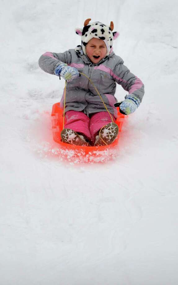 Eight-year-old Paige Fourtin, of Ansonia, sleds down the hill behind Derby Middle School Tuesday, Dec. 17, 2013. Photo: Autumn Driscoll / Connecticut Post