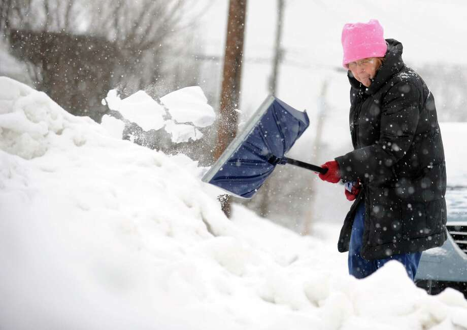 Carol Hunter shovels a space for her daughter to park in front of her house in Derby, Conn. Tuesday, Dec. 17, 2013. Photo: Autumn Driscoll / Connecticut Post