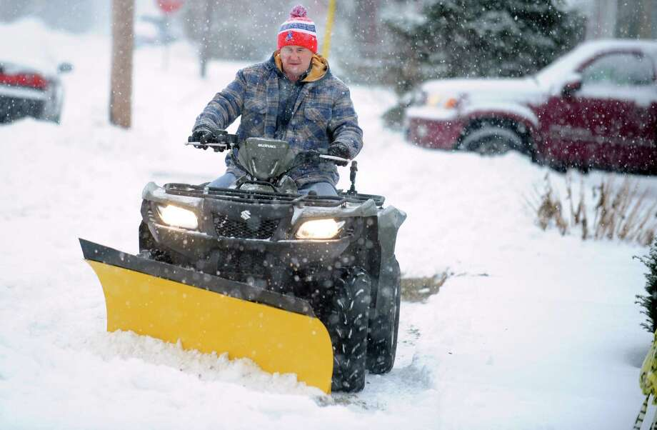 Dameon Kellogg uses a quad to plow the sidewalk near his home in Derby, Conn. Tuesday, Dec. 17, 2013. Photo: Autumn Driscoll / Connecticut Post