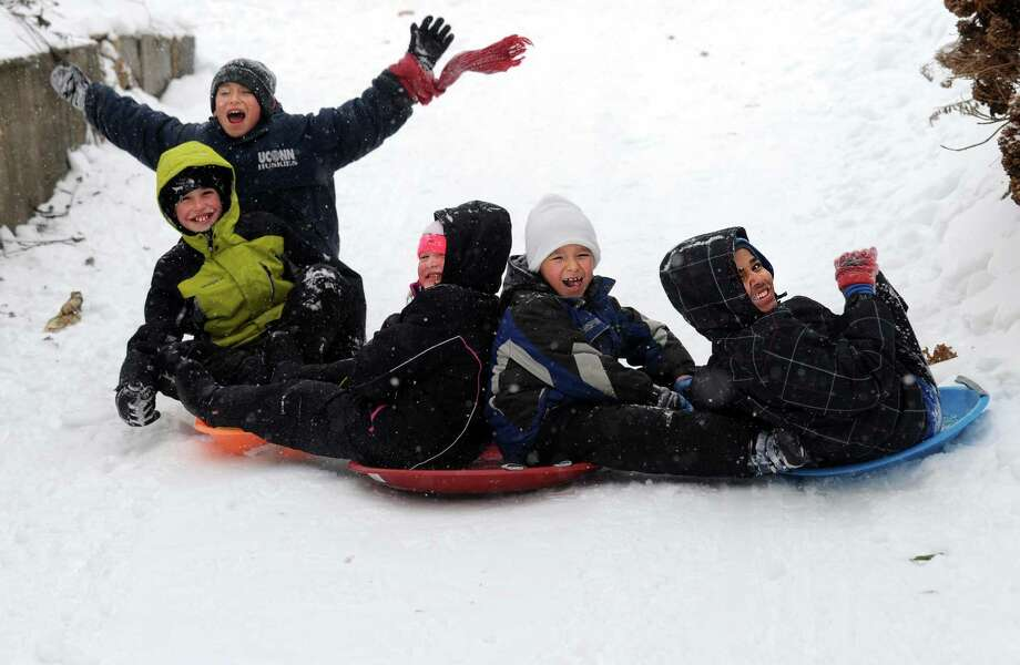 Friends, from left, Carlos Pinto, 10, Sean McDermott, 10, Riley McDermott, 8, Angel Pinto, 7, and Luis Santana, 12, sled down a driveway in Ansonia, Conn. Tuesday, Dec. 17, 2013. Photo: Autumn Driscoll / Connecticut Post