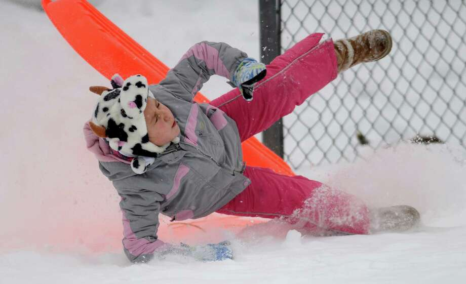 Eight-year-old Paige Fourtin, of Ansonia, takes a spill while sledding behind Derby Middle School Tuesday, Dec. 17, 2013. Photo: Autumn Driscoll / Connecticut Post