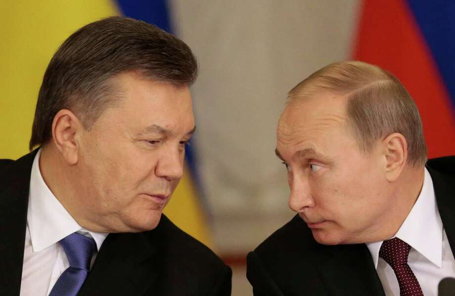 Russian President Vladimir Putin, right, and his Ukrainian counterpart Viktor Yanukovych chat during a news conference after their talks in Moscow on Tuesday, Dec. 17, 2013. Russian President Vladimir Putin says Moscow has agreed to sharply cut the price of its natural gas supplies to Ukraine and will buy $15 billion worth of Ukrainian government bonds, but says there was no discussion about Ukraine joining a free trade pact of three ex-Soviet nations. (AP Photo/Ivan Sekretarev) Photo: Ivan Sekretarev, STF / AP
