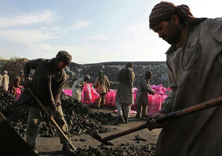 In this Thursday Dec. 5, 2013 photo, workers fill plastic bags with charcoal believed to be from Somalia at a charcoal trading facility in Sharjah, United Arab Emirates. Charcoal from Somalia is prized in Gulf nations: Made from acacia trees, it's slow burning and gives a sweet aroma to the region's beloved grilled meats and waterpipes. It is also banned by the United Nations, because its shipments rake in millions of dollars a year for al-Qaida-linked militants. (AP Photo/Kamran Jebreili) Photo: Kamran Jebreili, STF / AP