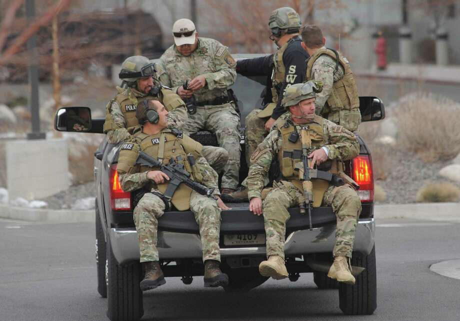 SWAT team members are taken to the Renown Regional Medical Center campus in Reno, Nev., where police went from door to door looking for a gunman who shot to death one person, wounded two others and killed himself. Photo: Tim Dunn / Reno Gazette-Journal / Reno Gazette-Journal