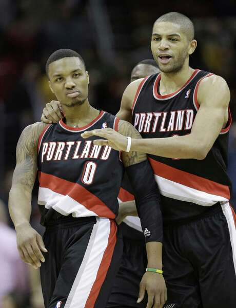 Portland guard Damian Lillard (left) is congratulated by Nicolas Batum after the former's second game-winning basket in as many outings. Photo: Tony Dejak / Associated Press / AP