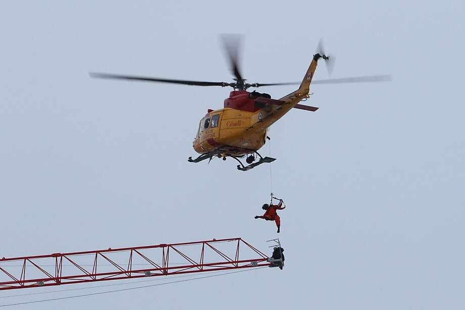 A rescue worker is lowered from a Canadian military helicopter as they retrieve a crane operator who was stranded atop a crane when fire broke out in an apartment building under construction in downtown Kingston, Ontario, Tuesday, Dec. 17, 2013. The crane operator was taken to a waiting ambulance, and police say he was believed to have only minor injuries. (AP Photo/The Canadian Press, Lars Hagberg) Photo: Lars Hagberg, Associated Press