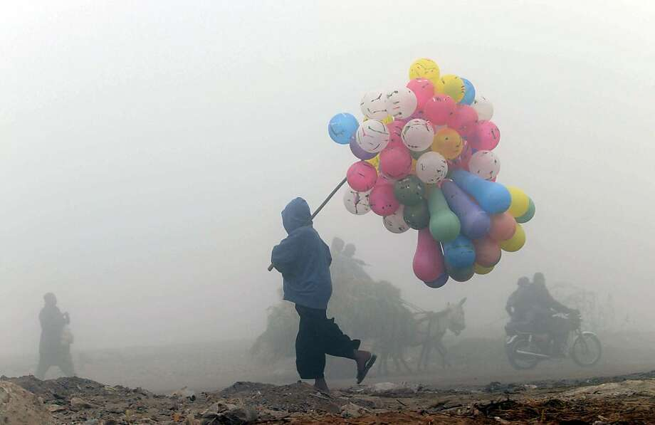 A Pakistani balloon vendor walks through a cold and foggy morning in Lahore on December 17, 2013. Ongoing foggy weather in Punjab and other parts of the country has badly affected flight and rail schedules. TOPSHOTS  AFP PHOTO/ARIF ALIArif Ali/AFP/Getty Images Photo: Arif Ali, AFP/Getty Images