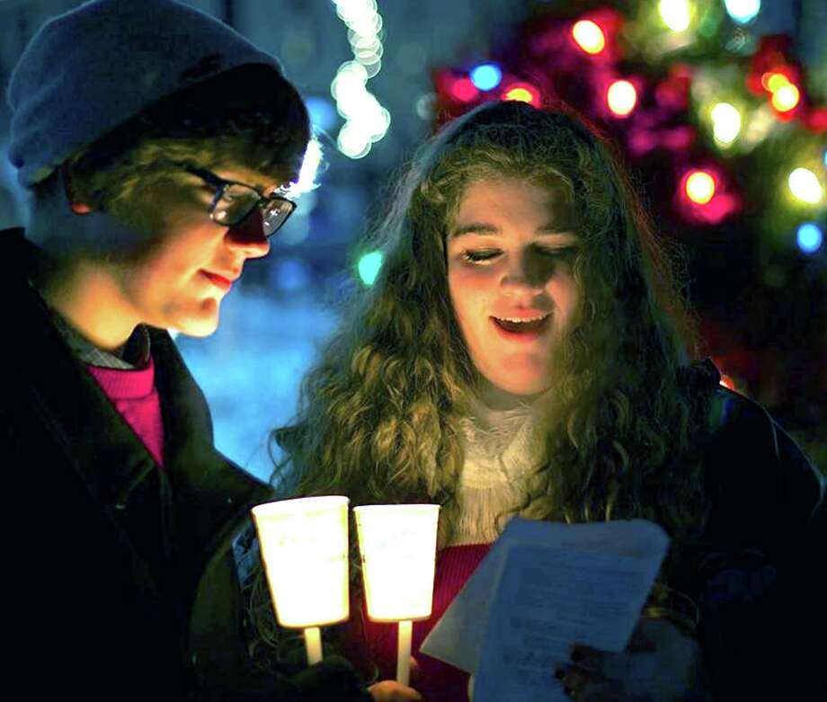 "'Silent Night'  Frigid temperatures didn't deter many Greater New Milford-area residents, young and old, from venturing Monday, Dec. 16, 2013 to the Village Green in New Milford for the town's traditional Carol Sing. Above, Josie Harding, 15, and her brother, Jack, 14, of New Milford are a postcard image as they join fellow carolers to sing ""Silent Night.""  For more photos, see the Dec. 27 edition of The Spectrum and visit www.newmilfordspectrum.com. Photo: Trish Haldin / The News-Times Freelance"
