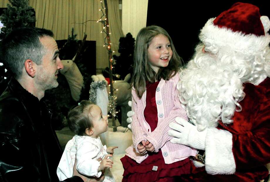 Nine-month-old Elsabeth Brass of New Milford finds her first Santa Claus experience an absolute eye opener as big sister Audrey, 6, bonds with the big guy. Looking on in rapt enjoyment is the girls' father, Peter Brass, during Washington's festive Holiday in the Depot. Dec. 13, 2013 Photo: Walter Kidd / The News-Times Freelance