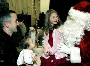 Nine-month-old Elsabeth Brass of New Milford finds her first Santa Claus experience an absolute eye opener as big sister Audrey, 6, bonds with the big guy. Looking on in rapt enjoyment is the girls' father, Peter Brass, during Washington's festive Holiday in the Depot. Dec. 13, 2013