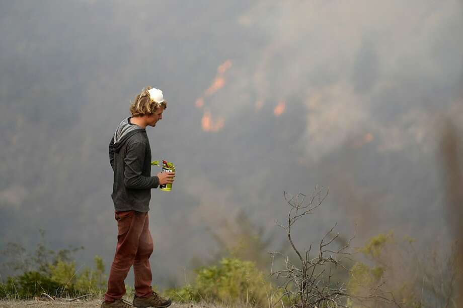 Garritt Cooper, 25, of Idaho takes a water break while clearing a fire break near a friend's home on Rancho Rico Road as firefighters battle a fire across the ridge in Big Sur, Calif., Tuesday Dec. 17, 2013. Firefighters are making gains against the unusual fall wildfire that has destroyed 15 homes and forced about 100 people to flee the forested mountains of California's scenic Big Sur region overlooking the Pacific. The fire began Sunday near midnight, fueled by dry vegetation and fanned by winds.(AP Photo/Monterey County Herald, David Royal) Photo: David Royal, Associated Press