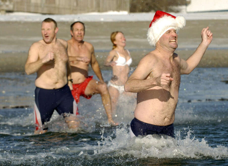 These hearty souls dashed across Compo Beach and into chilly Long Island Sound during Team Mossman's 2009 Polar Plunge. Five years later, the 11th annual plunge is set for New Year's morning as a fundraiser for Save the Children. Photo: File Photo, ST / Westport News