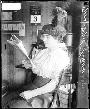This portrait shows Mrs. Byrd Winters reading a newspaper, sitting in front of a desk with framed prints and a calendar hanging on the wall in the background in a room in Chicago in 1914. Winters, his wife, Byrd Winters, and W. H. Cooper, a boarder of theirs, were charged with conspiracy to murder Winters' daughter and burn the body. From the Chicago Daily News collection. Photo: Chicago History Museum, Getty Images / Property of Chicago Historical Society.  Not to be reproduced or used without written permission from CHS Rights & Reproductions Dept.