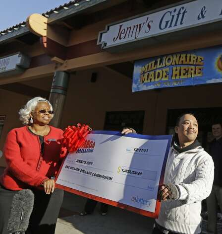 Jenny's Gift Shop owner Thuy Nguyen, right, accepts a $1 million check from California lottery sales representative Mona Sanders Wednesday in San Jose. Two lucky winning tickets were sold in Tuesday's near-record $636 million Mega Millions drawing: one at a tiny newsstand in Atlanta, and the other more than 2,000 miles away in California. Thuy Nguyen, says he doesn't know who the bought the winning ticket, but it's likely someone he knows, as most of his customers are his friends. Photo: Ben Margot, Associated Press
