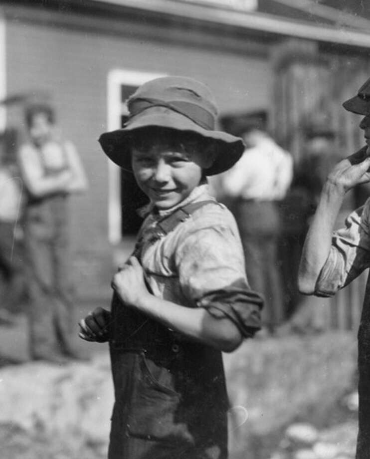 Ten year old Charlie Foster smiles while at his steady job in the Merrimack Mills factory at Huntsville, Ala. in 1914. His father stated that the boy is unable to read, but still he works at the mill instead of being in school. Photo: Buyenlarge, Getty Images / Archive Photos