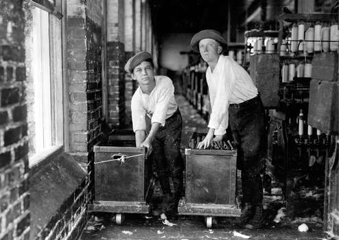 This portrait shows a pair of young boys at work in the weave room of an Alabama cotton mill. Photo: Buyenlarge, Getty Images / Archive Photos