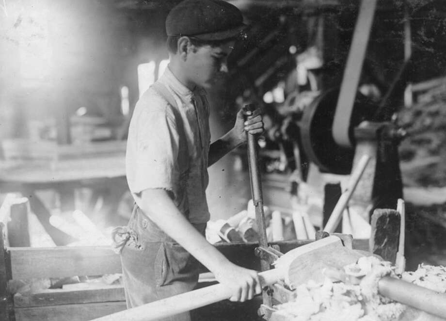 A fifteen-year-old boy in Denison, Texas operating a dangerous boring machine at which he said a boy recently bored half his hand off. To operate this machine (which bores a large hole in the spade handle) the boy has to throw his whole weight onto the lever which pushes the handle (and himself) up against the unprotected borer. A slip might easily prove fatal. The boy earns $1.65 a day. This factory has a number of unprotected belts and dangerous machines. One other boy, about the age of this one, was doing all kinds of work, taking away the handles from a huge rip saw, etc., and constantly exposed to danger. Photo: Buyenlarge, Getty Images / 2010 Buyenlarge