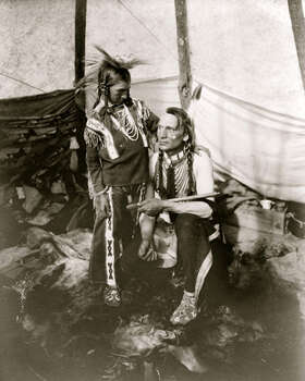 A Siksika man with calumet and young boy are pictured inside tepee. Photo: Buyenlarge, Getty Images / Archive Photos