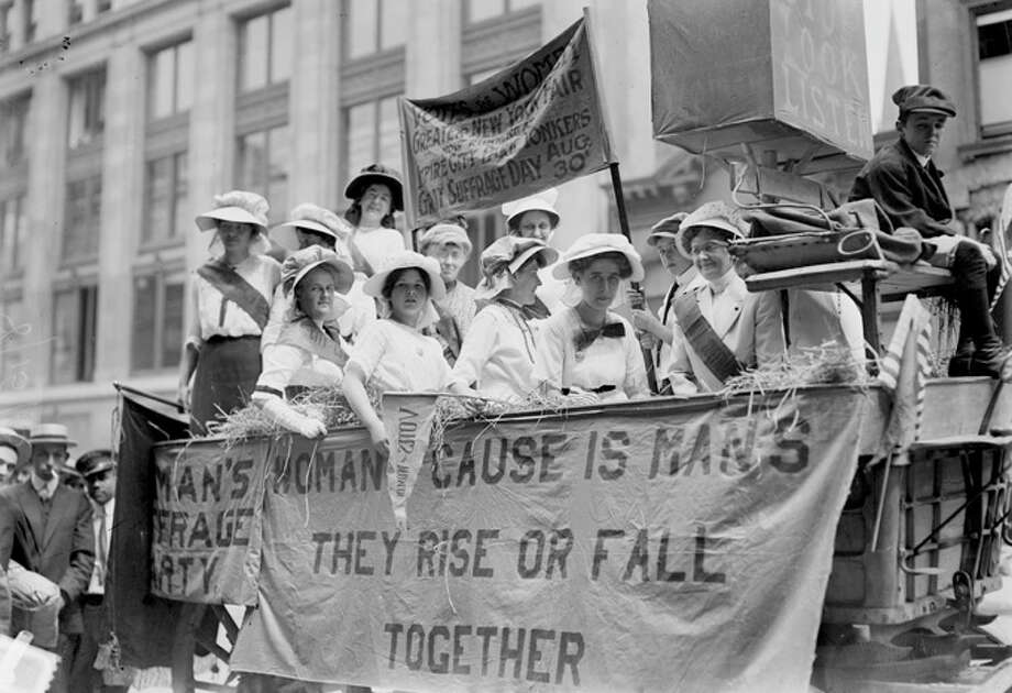 This close-up show a large group of suffragists as they ride in a hay wagon adorned with slogans in 1914. One slogan reads 'Woman's Cause is Man's; They Rise Or Fall Together.' Photo: Buyenlarge, Getty Images / Archive Photos