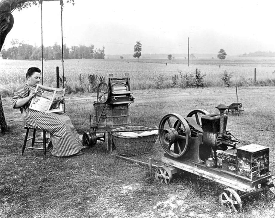 Somewhere in the American Midwest, a woman sits and reads the newspaper, while waiting for her gas powered washing machine to finish a load of clothing. Photo: PhotoQuest, Getty Images / Archive Photos