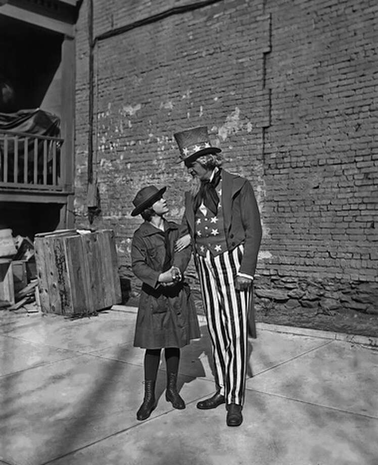 A Girl Scout with a man dressed as Uncle Sam circa 1914. Photo: FPG, Getty Images / 2011 Getty Images