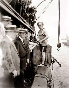 Escapologist Harry Houdini, born Erik Weisz, prepares to perform one of his most famous publicity stunts, the overboard box escape, in New York's East River, circa 1914.  Houdini was locked in handcuffs and leg-irons, then nailed into the crate which was roped and weighed down with two hundred pounds of lead.  The crate was then lowered into the water, from which he escaped in fifty-seven seconds. Photo: Popperfoto, Popperfoto/Getty Images / Popperfoto