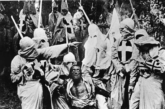Actors costumed in the full regalia of the Ku Klux Klan chase down a white actor in blackface in a still from 'The Birth of a Nation,' the first-ever feature-length film, directed by D. W. Griffith, California, 1914. Photo: Hulton Archive, Getty Images / 2005 Getty Images