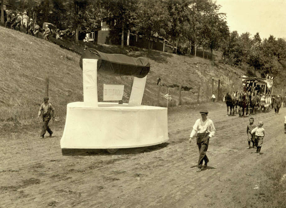 Watched by onlookers on a hill and young boys on the road, a vehicle in the shape of an iron travels a dirt road in an Independence Day parade, Springfield, Vt., July 4, 1914. Photo: Vintage Images, Getty Images / 2007 Getty Images