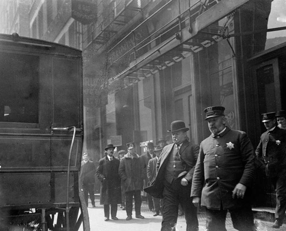 Reputed gangster James Franche and a policeman a walk toward an automobile parked along the street in Chicago, 1914. Franche, nicknamed, Duffy the Goat, confessed to murdering Isaac Henagow in the Roy Jones Cafe, located at 2037 South Wabash Ave. in the Near South Side area of Chicago. From the Chicago Daily News collection. Photo: Chicago History Museum, Getty Images / Property of Chicago Historical Society.  Not to be reproduced or used without written permission from CHS Rights & Reproductions Dept.