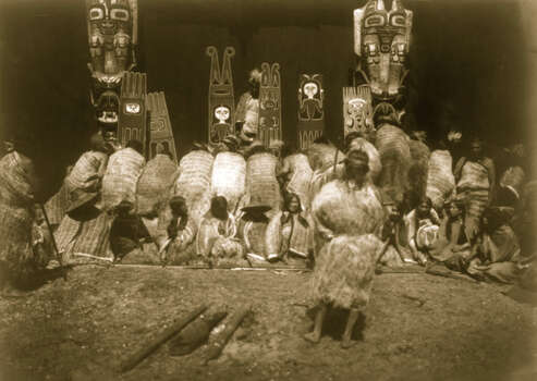 Kwakiutl people, some bowing before totem poles in the background, others seated facing forward are part of the nunhlim ceremony, the four days prior to the Winter Dance. Photo: Buyenlarge, Getty Images / Archive Photos