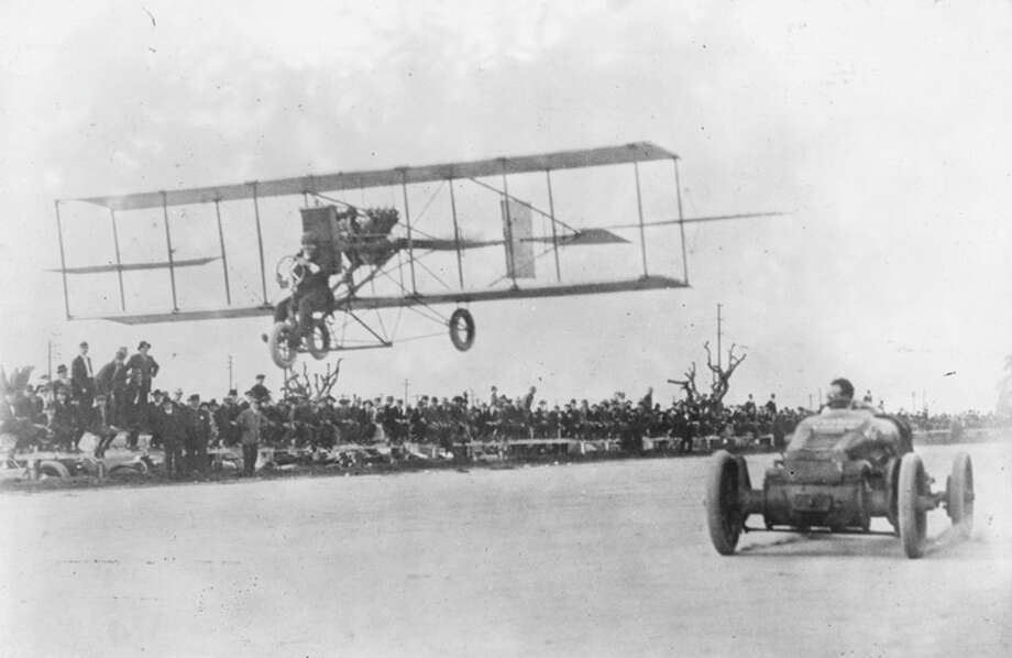 An early flying machine races against a car. Photo: Getty Images