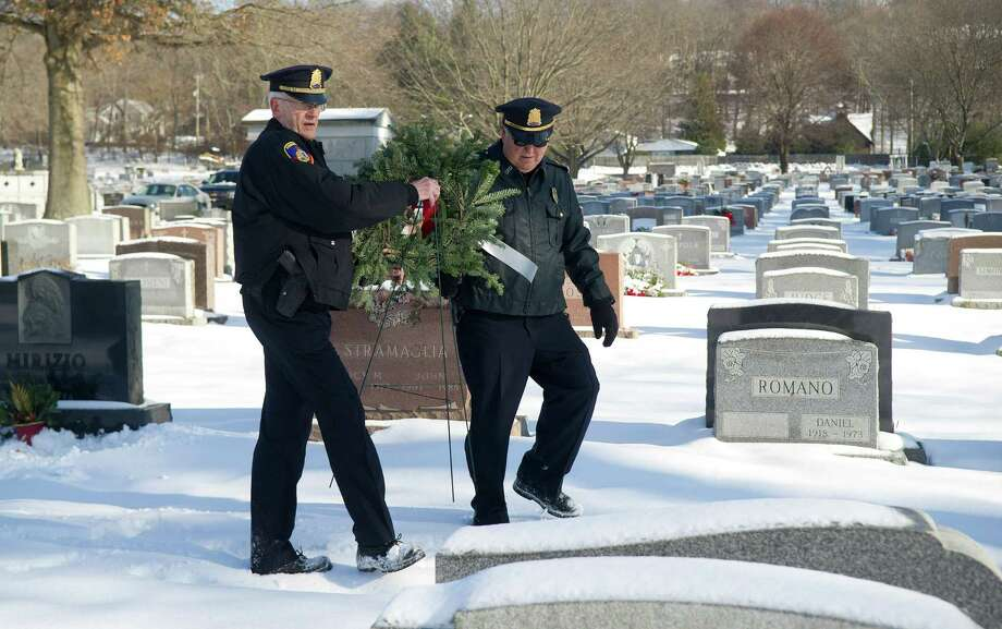Stamford police Captains Greg Tomlin, left, and Bill Mullin, right, place a wreath at the grave of William McNamara at St. John's Cemetery in Darien, Conn., on Wednesday, December 18, 2013.  McNamara was a police officer who was shot and killed during a liquor store holdup 40 years ago. Photo: Lindsay Perry / Stamford Advocate