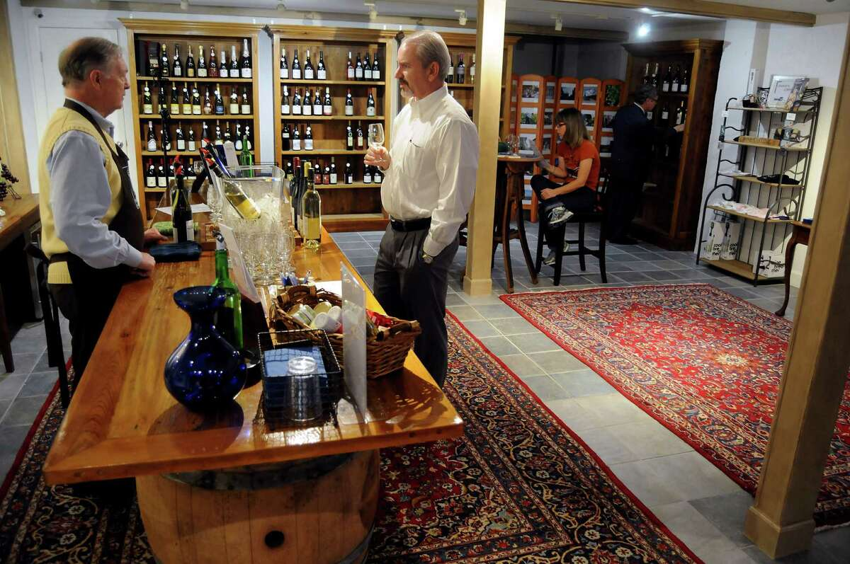 Tim Smith, left, serves wine during a free tasting in the new cellar at French Country Wines.