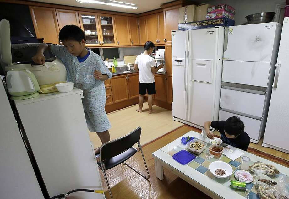 In this Oct. 29, 2013 photo, North Korean defectors, from left, Ju Cheol-kwang, Hwang Cheol-jin and Han Jin-beom eat dinner at their home in Seoul, South Korea. The three are among nine boys - all defectors from North Korea - reared by South Korean Kim Tae-hoon who  has given them their first real experience of family. (AP Photo/Lee Jin-man) Photo: Lee Jin-man, Associated Press