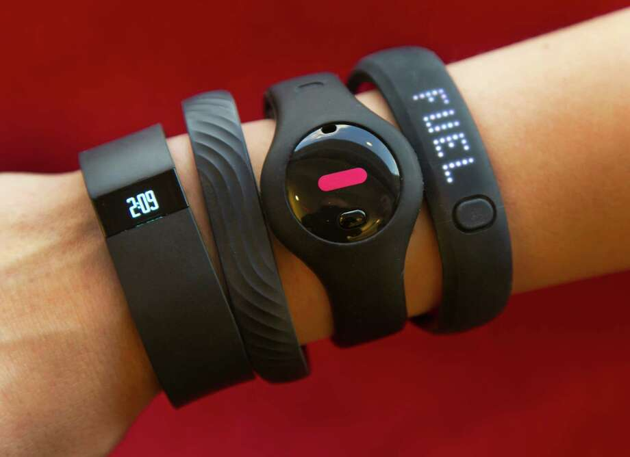 Four fitness trackers are shown in this photograph, in New York,  Monday, Dec. 16, 2013. They are, from left, Fitbit Force, Jawbone Up, Fitbug Orb, and the Nike FuelBand SE. For aspiring health nuts and to inspire couch potatoes to get active, the latest crop of fitness gadgets will record much more than how many steps you took on any given day. From sleep patterns to calorie intake, mood and progress toward exercise goals, few aspects of life are left un-tracked for those in search for a more quantified self. (AP Photo/Richard Drew) Photo: Richard Drew, Associated Press / Associated Press contributed
