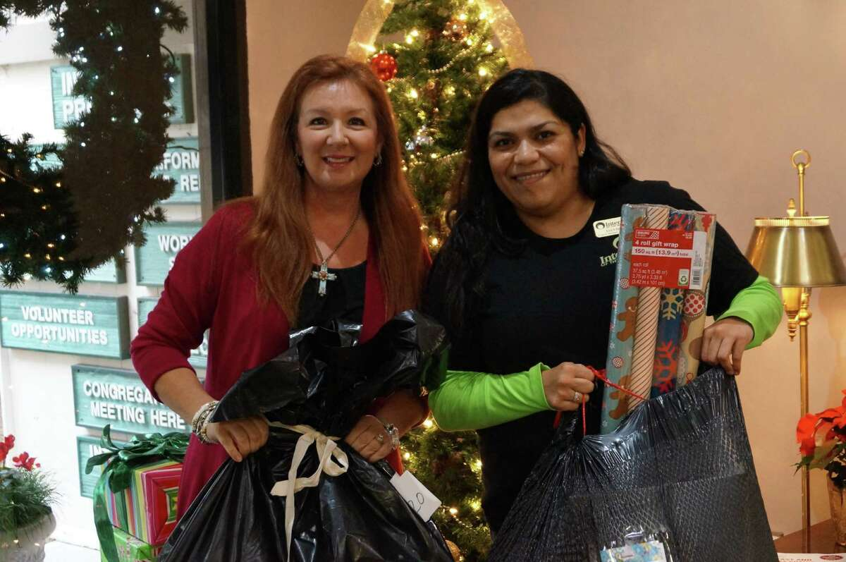 Teresa Yniguez, left, and Lucy Gomez, family services mManager at Interfaith of The Woodlands deliver a donation as part of Interfaith's holiday giving program.