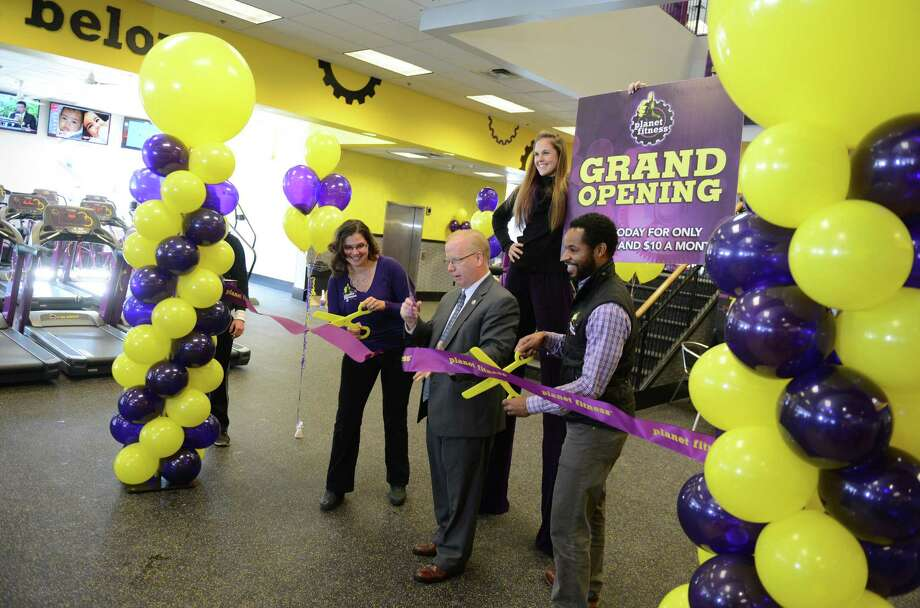 Danbury Mayor Mark Boughton, center, cuts the ribbon at the grand opening of Planet Fitness in Danbury with co-owners Raynya Simmons and Jason Price on Wednesday, Dec. 18, 2013.  The 24-hour gym is located on Federal Road, filling the space where Borders used to be.  The Danbury Planet Fitness location is 26,000 sq. ft., featuring more than 100 cardio machines, full locker rooms, nearly 30 55-inch flat-screen televisions, two circuit stations for express workouts and abs, eight tanning booths and more. Photo: Tyler Sizemore / The News-Times