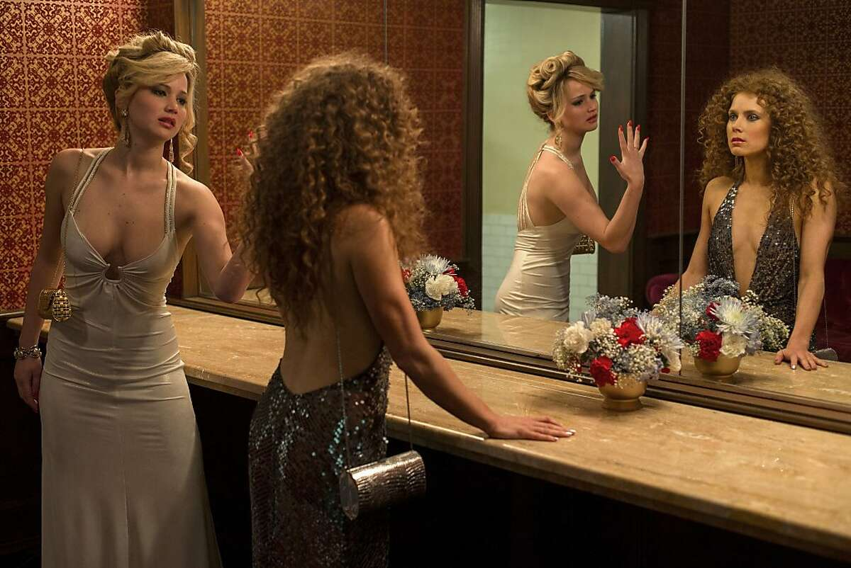 Rosalyn Rosenfeld (Jennifer Lawrence) & Sydney Prosser (Amy Adams) in the Grand Old AC Hotel powder room in Columbia Pictures' AMERICAN HUSTLE. (Jennifer Lawrence dress: made for film, jewelry, shoes: vintage / Amy Adams dress: made for film, jewelry, shoes: vintage)