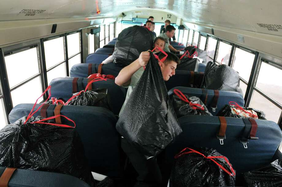 Christian Brothers Academy senior Nick Makarowsky, foreground, and seventh grader Tucker Scaringe, background, load bags of items onto a bus  Wednesday morning, Dec. 18, 2013, at CBA in Albany, N.Y. The students were loading the items on the bus to be transported to an elementary school.  The school has been working with an Albany public elementary school for over five years helping out between 30 to 35 children a year. Each child is given a toy, a book, a blanket, sneakers or boots and a jacket.  (Paul Buckowski / Times Union) Photo: PAUL BUCKOWSKI / 00025053A