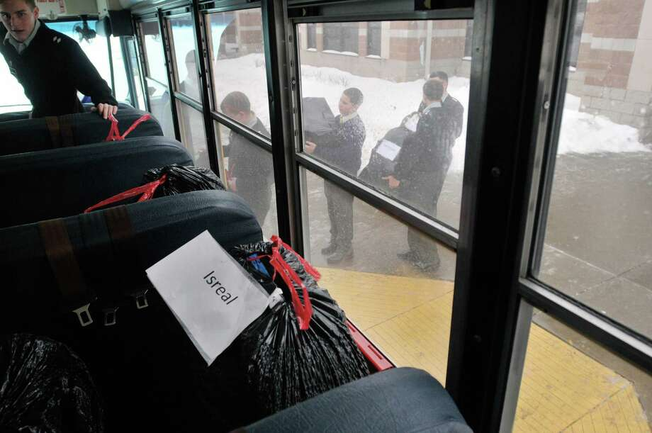 Christian Brothers Academy in the National Honor Society line up outside a bus with bags of items Wednesday morning, Dec. 18, 2013, at CBA in Albany, N.Y. The students were loading the items on the bus to be transported to an elementary school.  The school has been working with an Albany public elementary school for over five years helping out between 30 to 35 children a year.  Each child is given a toy, a book, a blanket, sneakers or boots and a jacket.   (Paul Buckowski / Times Union) Photo: PAUL BUCKOWSKI / 00025053A