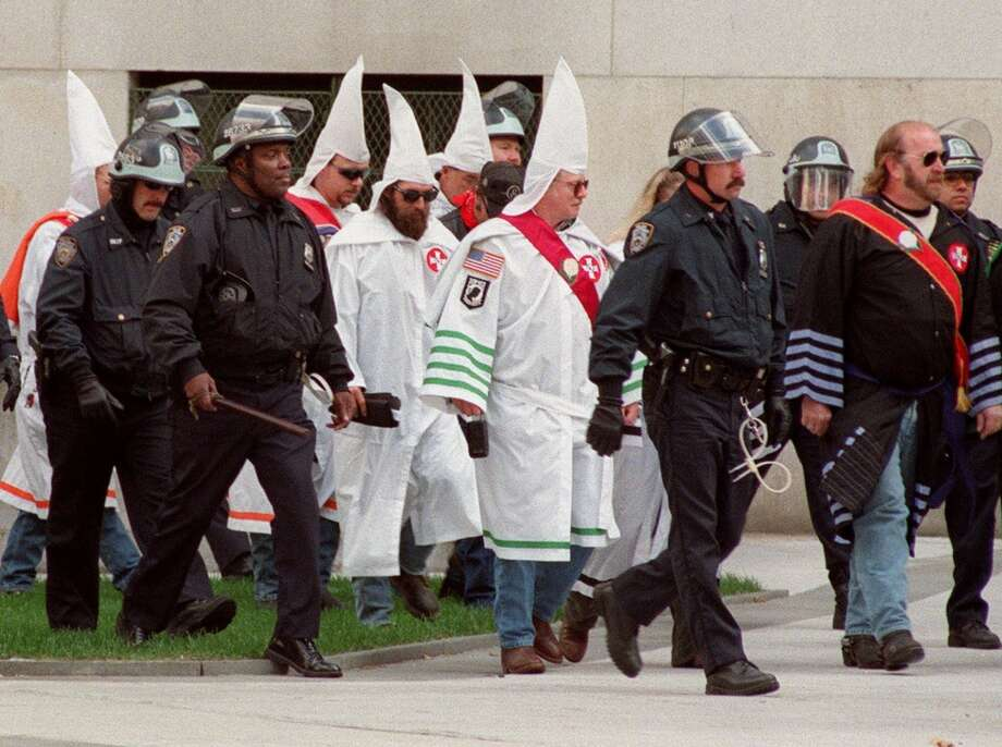 Members of the Ku Klux Klan, led by the Rev. Jeffrey L. Berry,  national Imperial Wizard for the KKK Church of the American Knights, right, are escorted to a KKK rally held outside the Criminal Court Building Saturday, Oct. 23, 1999 in New York.  (AP Photo/Mitch Jacobson) Photo: AP