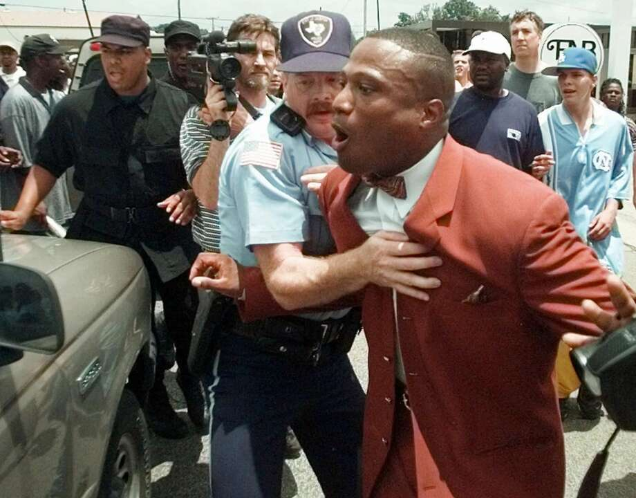 Quanell X, right, a Muslim leader from Houston, is restrained by a Jasper police officer as he yells at a member of the Ku Klux Klan after their rally Saturday, June 27, 1998, in Jasper, Texas. The KKK held a rally to denounce the dragging death of James Byrd Jr. Black counterdemonstrators carrying guns showed up and police kept the two sides apart, making one arrest as the Klan rally ended. (AP Photo/David J. Phillip) Photo: AP