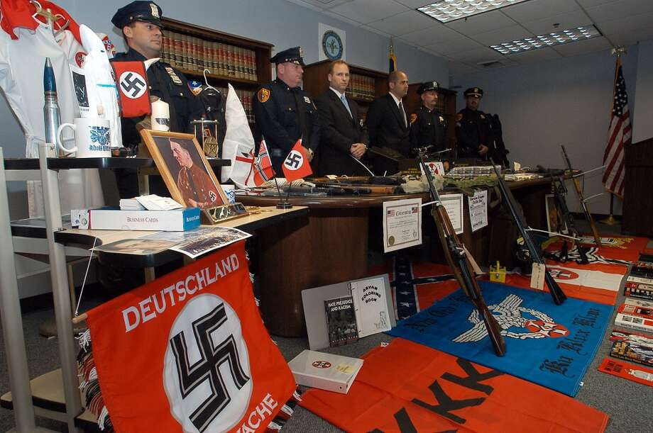 Suffolk County police officers stand behind some of the items confiscated during a search warrant of the home of Joseph Donato, Jr. Sunday, May 25, 2003, in Hauppauge, N.Y. The Suffolk County District Attorney's Office announced that they had arrested Donato Friday on weapons charges. Police confiscated dozens of weapons, a Ku Klux Klan gown and hood, and other apparel adorned with swastikas and racist emblems. (AP Photo/Ed Betz) Photo: AP