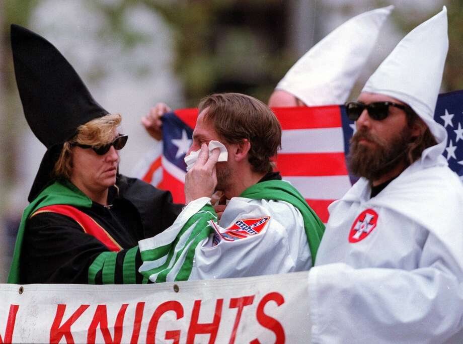 James Sheeley, center, of the New York and New Jersey Ku Klux Klan, wipes a scrape on his cheek that he received in a scuffle with an unidentified anti-KKK protester at the start of a KKK rally in New York, Saturday, Oct. 23, 1999. An unidentified Klan member tends to Sheely, left, as another Klansman looks on, right. (AP Photo/Ed Betz) Photo: AP