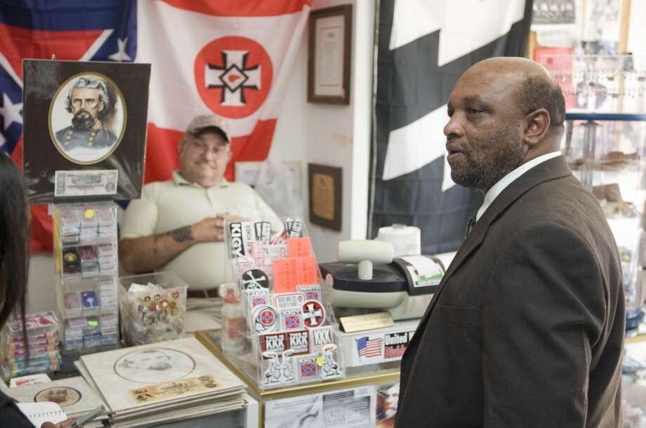 FILE - In a Wednesday, Feb. 27, 2008 file photo, Rev. David Kennedy, right, looks at items as John Howard watches him inside The Redneck Shop in Laurens, S.C. A judge has ruled that Kennedy's church, the New Beginnings Baptist Church, is the rightful owner of the building where The Redneck Shop is located.  New Beginnings sued John Howard and others in 2008, saying the property was transferred to the church in 1997 by a Klansman fighting with others inside the hate group. (AP Photo/Patrick Collard,File) Photo: Associated Press
