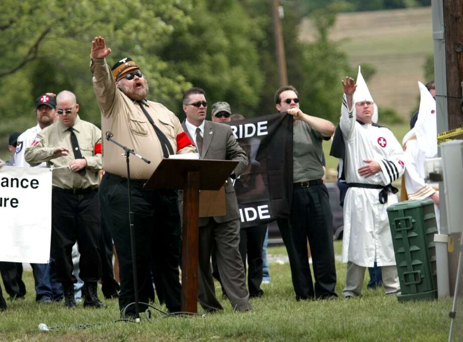 Ken Krauss of the National Socialist Movement, center, salutes with members of the Ku Klux Klan, Saturday, June 10, 2006, at the Antietam National Battlefield in Sharpsburg, Md. About 30 people, some in white robes and others in the military-style clothing and swastika armbands of the National Socialist Movement of America, stood next to a farmhouse on the battlefield. (AP Photo/Matt Houston) Photo: AP