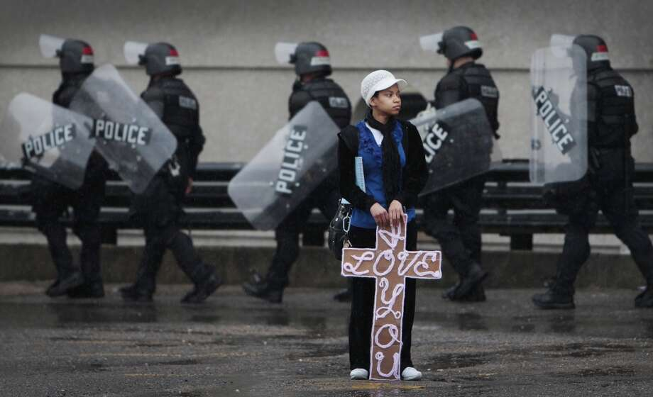 As Memphis Police in riot gear lineup Alvianca McLemore holds a sign of love in a holding area on Adams while waiting for a KKK rally in Memphis, Tenn. Saturday, March 30, 2013. The Ku Klux Klan announced plans to protest in Memphis after the Memphis City Council renamed three Confederate-themed city parks in February. (AP Photo/The Commercial Appeal, Mark Weber) Photo: Associated Press