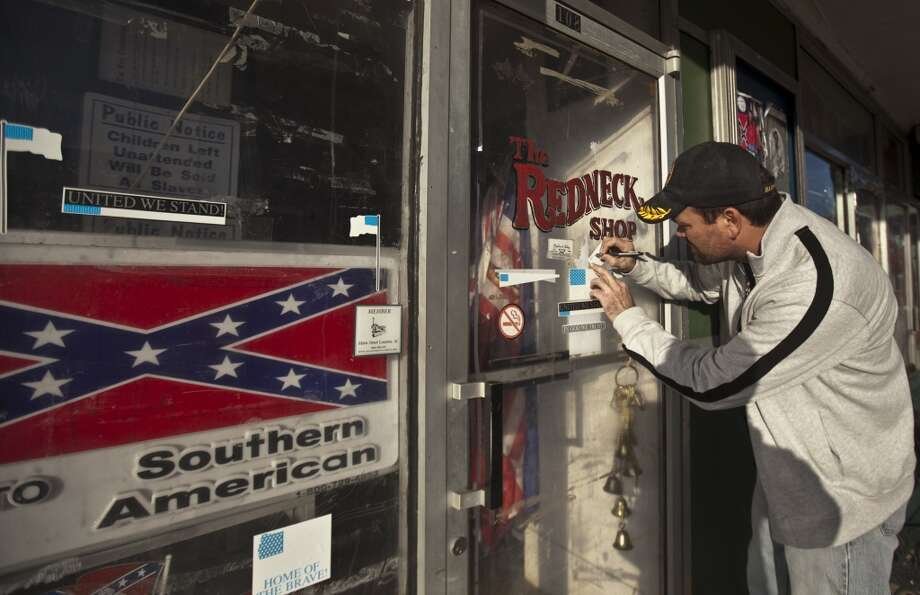 Sean Vick, after hearing about the possible closure, writes down the phone number of the Redneck Shop, which sells Klan and Confederate knick-knacks including infamous white robes, in Laurens, S.C., Jan. 4, 2011. Last month, a state circuit judge in Greenwood, S.C., decided that Rev. David KennedyâÄôs New Beginning Missionary Baptist Church holds the valid title to the old Echo Theater, which houses the Redneck Shop he has been fighting against for more than fifteen years. (John Adkisson/The New York Times) Photo: NYT